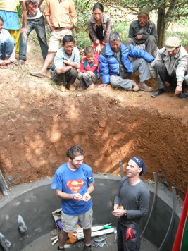 Talesnick (right) and a student in the biogas generator pit with Namsaling villagers looking on